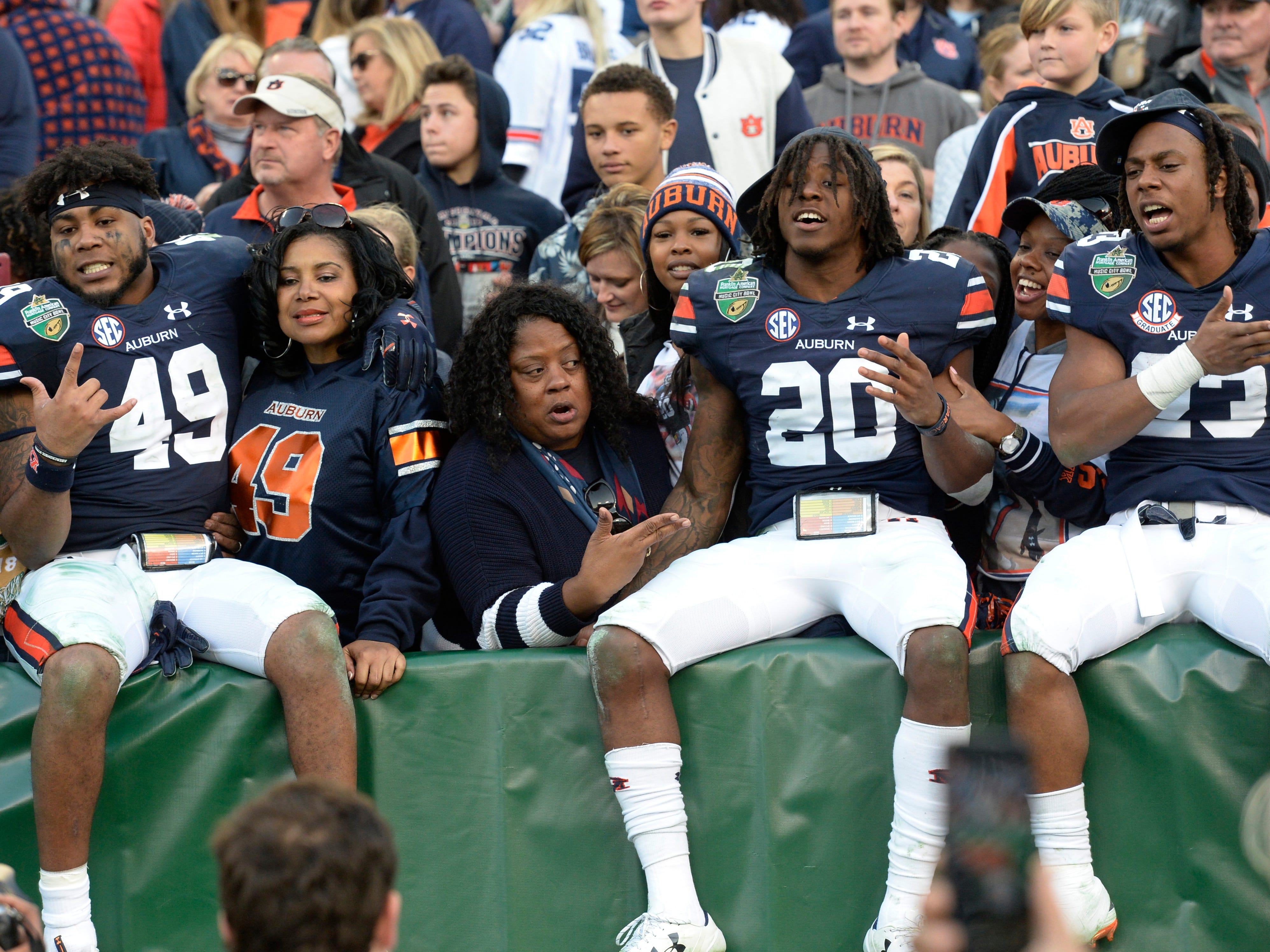 Auburn linebacker Darrell Williams (49), defensive back Jeremiah Dinson (20) and wide receiver Ryan Davis (23) celebrate in the stands after the team's 63-14 win over Purdue in the Music City Bowl NCAA college football game Friday, Dec. 28, 2018, at Nissan Stadium in Nashville, Tenn.