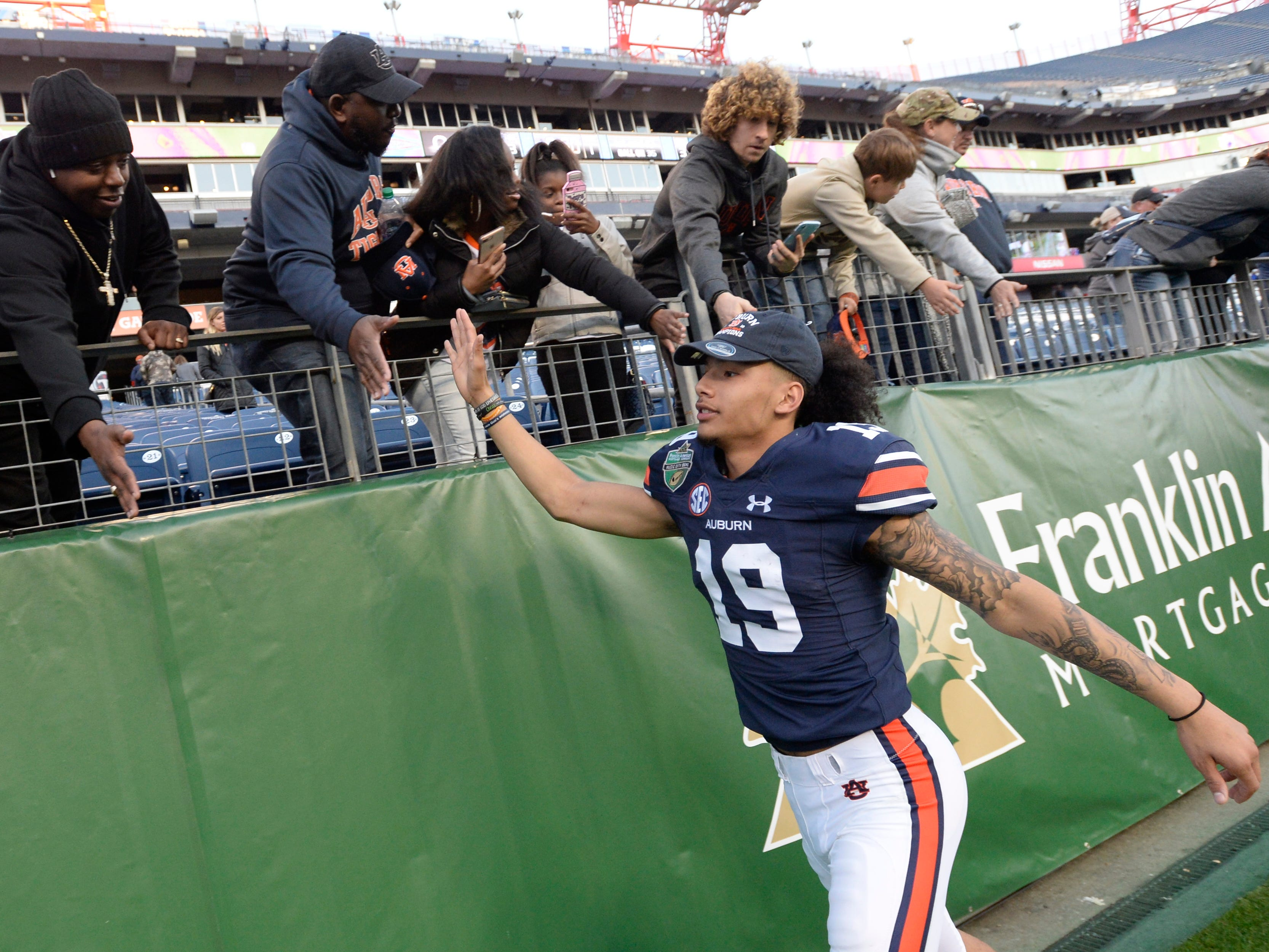 Auburn wide receiver Matthew Hill (19) slaps hands with fans after the Music City Bowl NCAA college football game Friday, Dec. 28, 2018, at Nissan Stadium in Nashville, Tenn.