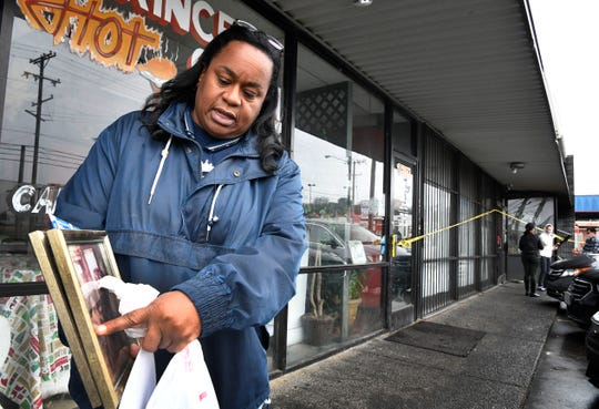 Semone Jeffries, whose mother has owned Prince's Hot Chicken Shack for 38 years, salvaged some family photos from inside the building after a vehicle crashed into a strip mall Friday, Dec. 28, 2018, on Ewing Drive, damaging Prince's and several other businesses.