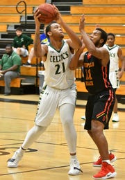 Trinity Catholic's Kyler Rodmon (21), one of two transfers for the Celtics, looks to shoot the ball with Deerfield Beach High School defender Michael Johnson (11) trying to get the block during the Kelleher Firm Gulfshore Holiday Hoopfest at Golden Gate High School.