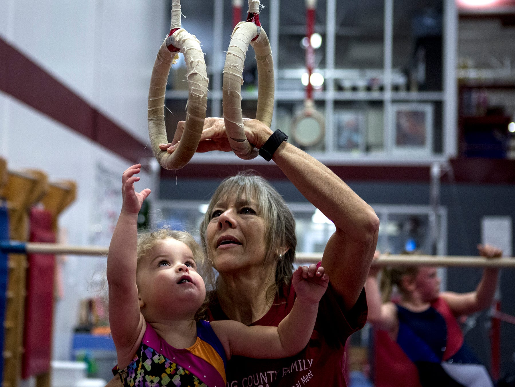 Jeanne Reid helps 2 year-old Eva Swick grab onto the rings and swing at a preschool open gymnastics class at the Licking County YMCA. The YMCA will be holding a second preschool open gym Friday January 4th in the Mitchell Center. Prices are $15 for members and $25 for nonmembers, ages 3-6.