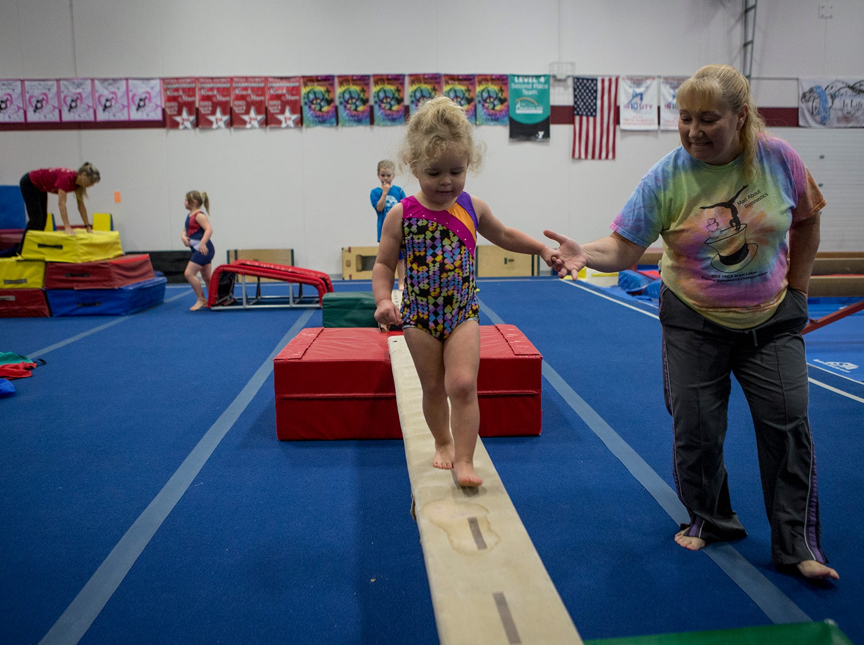 Diane Hodge holds Eva Swick's hand as she makes her way across the balance beam during a preschool open gymnastics class at the Licking County YMCA. The YMCA will be holding a second preschool open gym Friday January 4th in the Mitchell Center. Prices are $15 for members and $25 for nonmembers, ages 3-6.