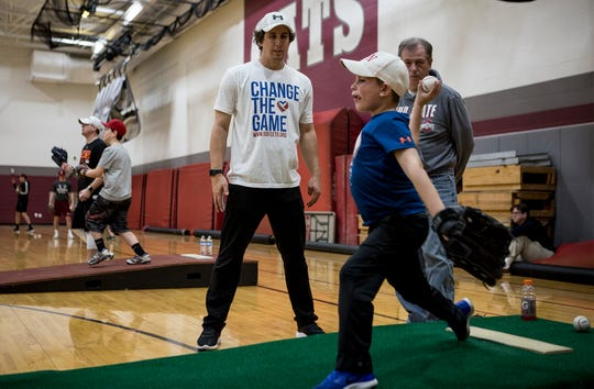 Dylan Hayes, 8, of Newark works on his pitching skills with Derek Holland, a professional pitcher who most recently pitched for the San Francisco Giants, while his grandfather, Keith Hayes watches. Holland, a Newark graduate, hosts a skills camp every year at Newark High School to help young kids work on their pitching.