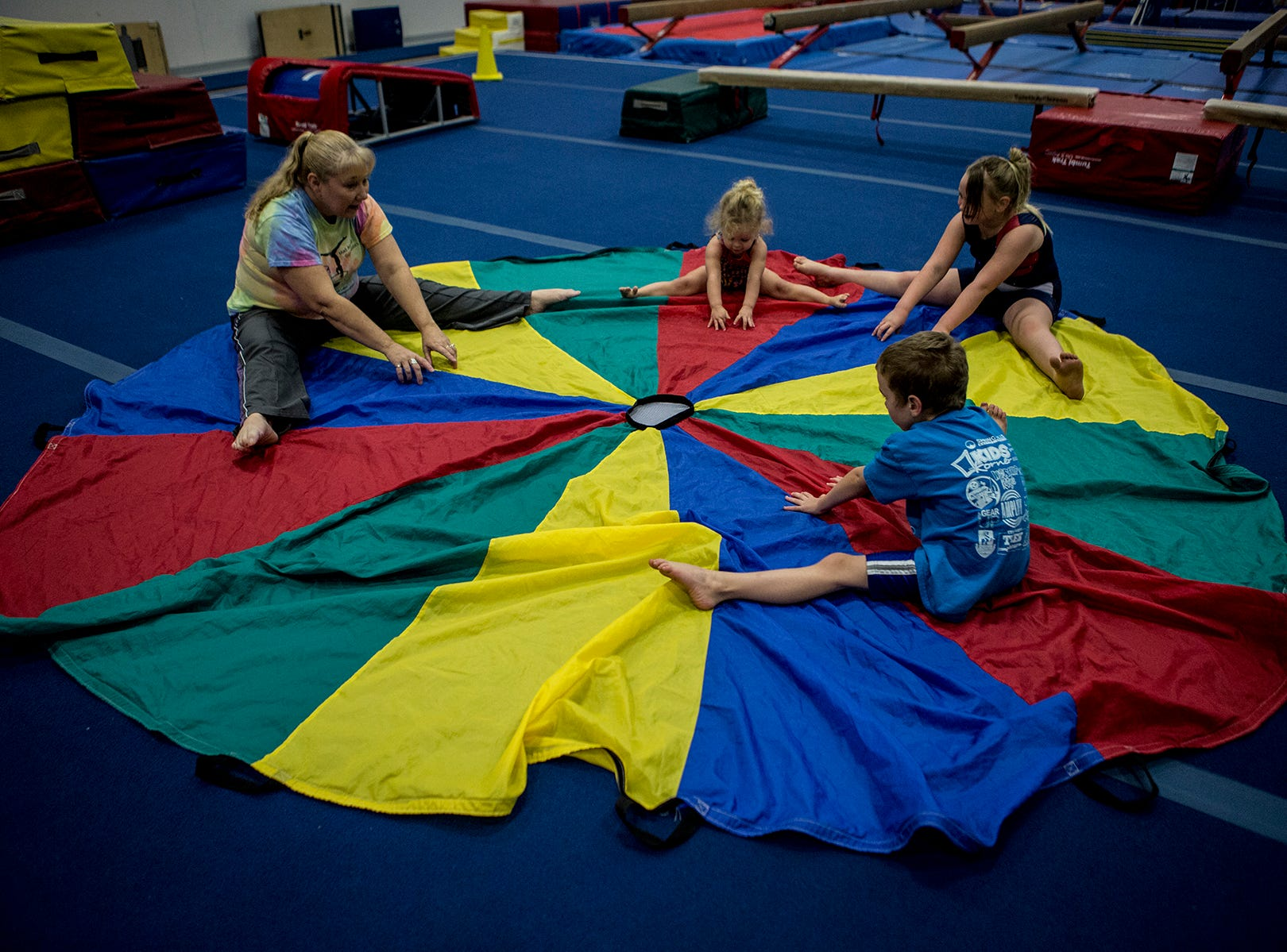Diane Hodge stretches with siblings Eva, Alyssa and Micaiah Swick during a preschool open gymnastics class at the Licking County YMCA. The YMCA will be holding a second preschool open gym Friday January 4th in the Mitchell Center. Prices are $15 for members and $25 for nonmembers, ages 3-6.