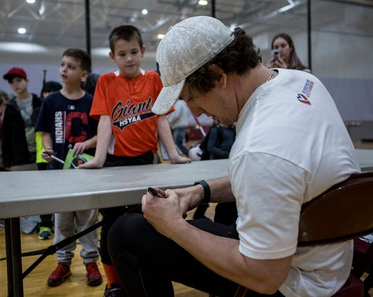 Derek Holland signs autographs after hosting a skills camp for area youth at Newark High School.