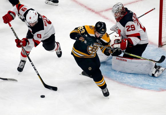 New Jersey Devils defenseman Will Butcher (8) clears the puck away from Boston Bruins left wing Brad Marchand (63) as Devils goaltender Mackenzie Blackwood (29) minds the net during the first period of an NHL hockey game Thursday, Dec. 27, 2018, in Boston.