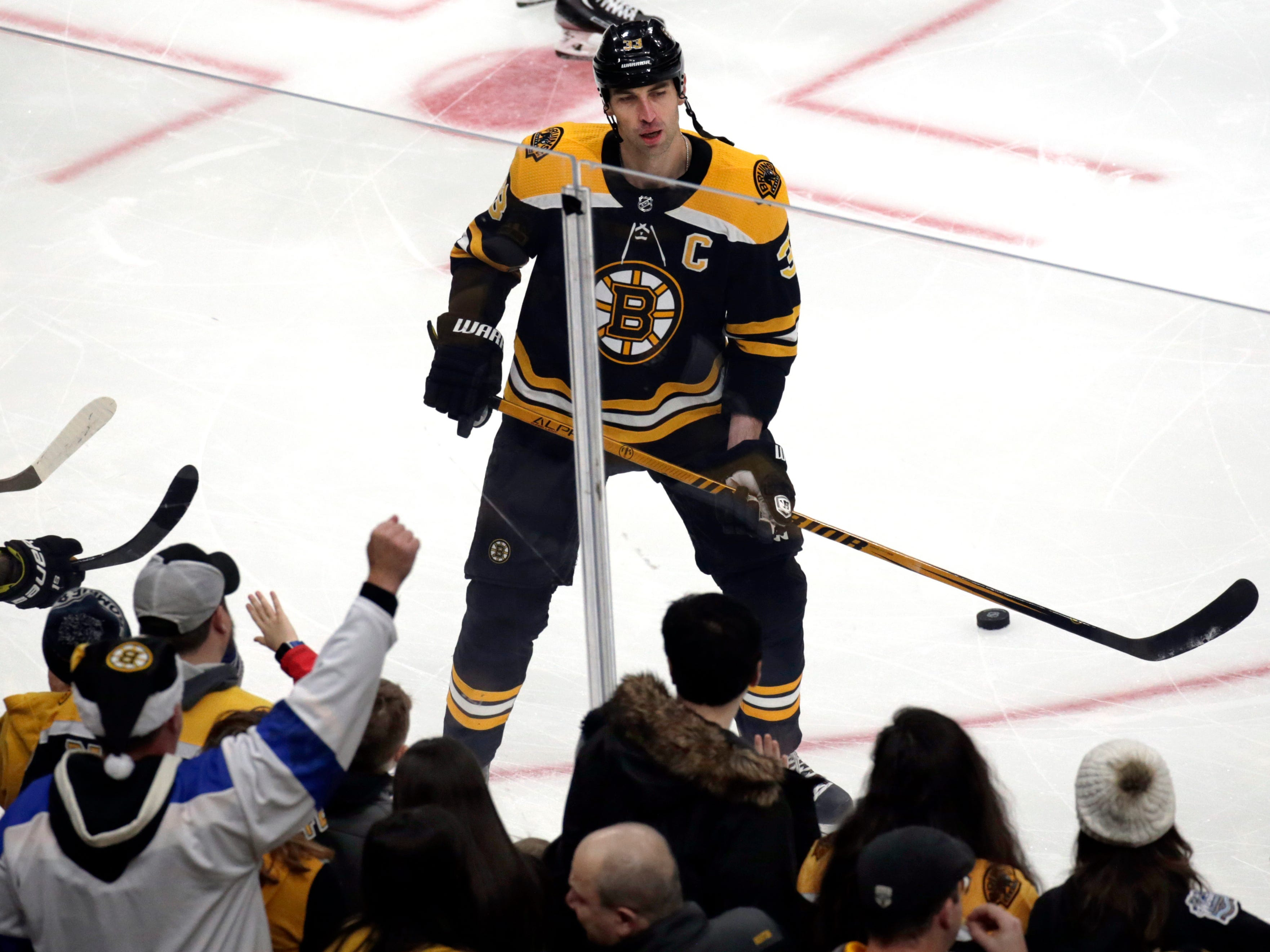 Fans gesture to Boston Bruins defenseman Zdeno Chara as he warms up prior to the team's NHL hockey game against the New Jersey Devils, Thursday, Dec. 27, 2018, in Boston. Chara is back after missing  19 games with an injury.