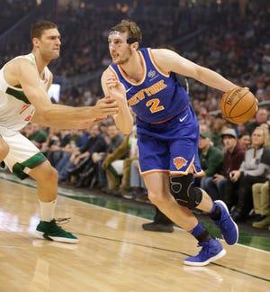 New York Knicks' Luke Kornet (2) drives against Milwaukee Bucks' Brook Lopez during the first half of an NBA basketball game Thursday, Dec. 27, 2018, in Milwaukee.