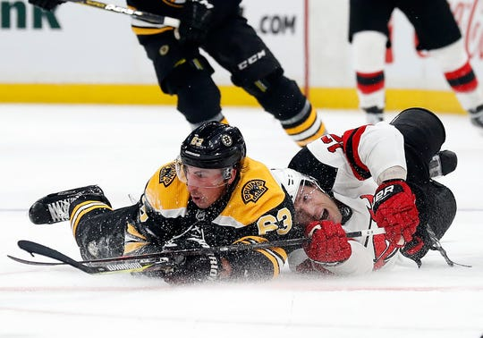 Dec 27, 2018; Boston, MA, USA; Boston Bruins left wing Brad Marchand (63) and New Jersey Devils defenseman Ben Lovejoy (12) battle for the puck at center ice during the second period at TD Garden.