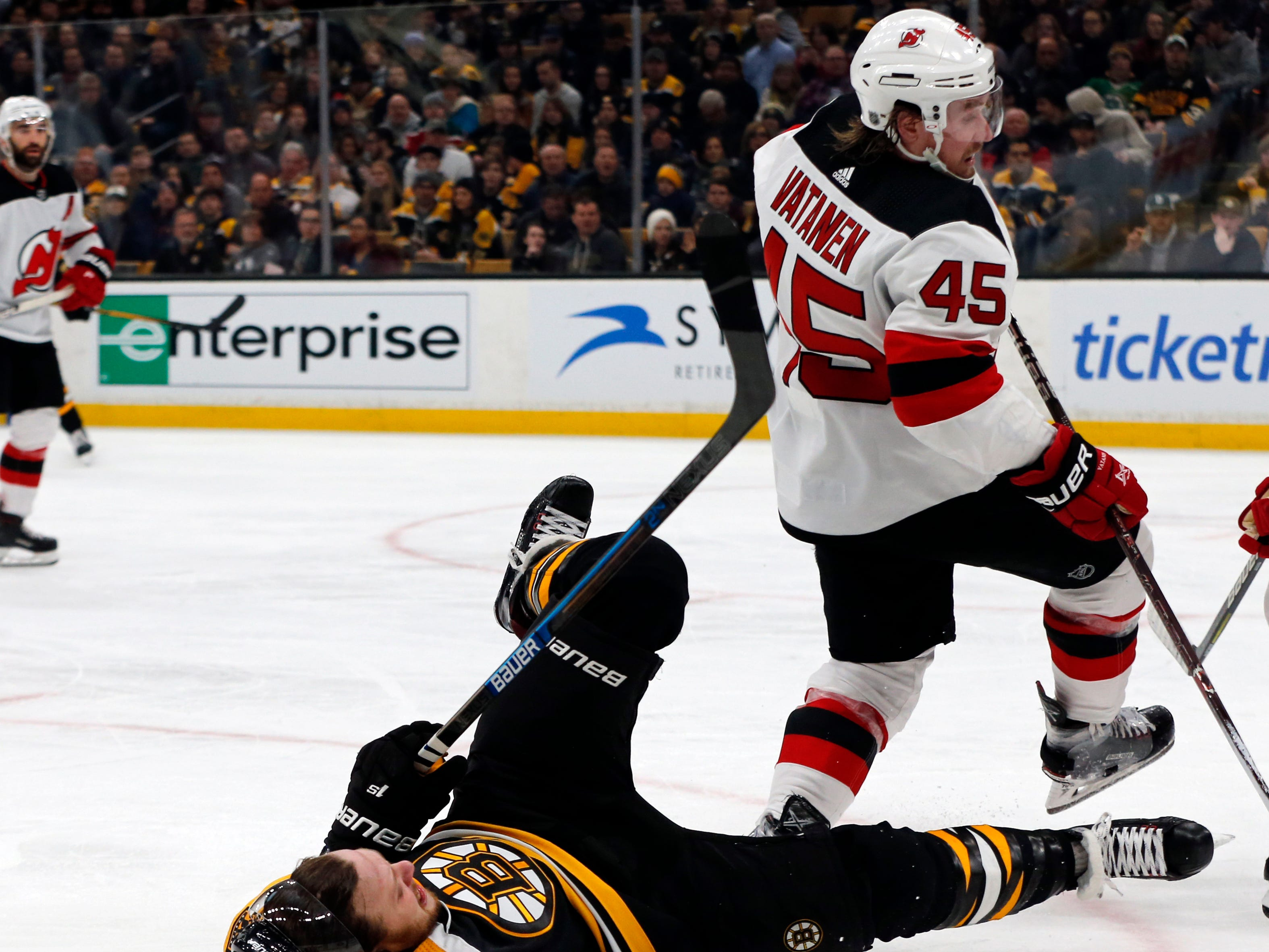 Boston Bruins right wing David Pastrnak (88) is knocked to the ice as he competes with New Jersey Devils defenseman Sami Vatanen (45) for the puck the second period of an NHL hockey game Thursday, Dec. 27, 2018, in Boston