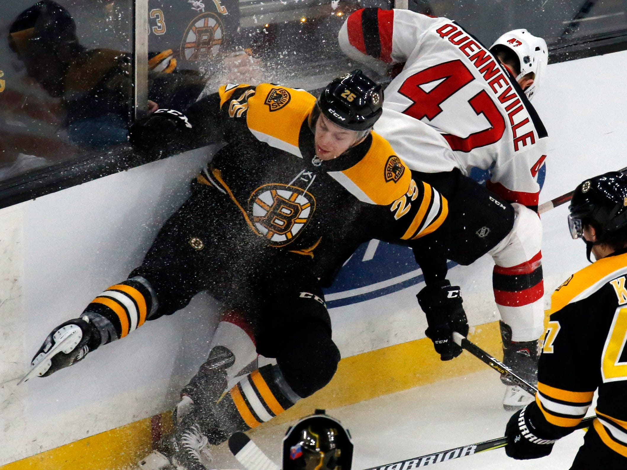 Boston Bruins defenseman Brandon Carlo (25) and New Jersey Devils center John Quenneville (47) compete for the puck along the boards during the first period of an NHL hockey game Thursday, Dec. 27, 2018, in Boston.