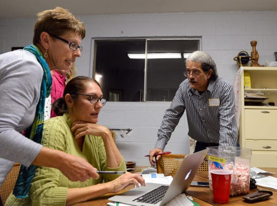 Anselmo Delgado-Martinez speaks to two volunteers trying to arrange migrant travel plans at El Calvario United Methodist church in Las Cruces.