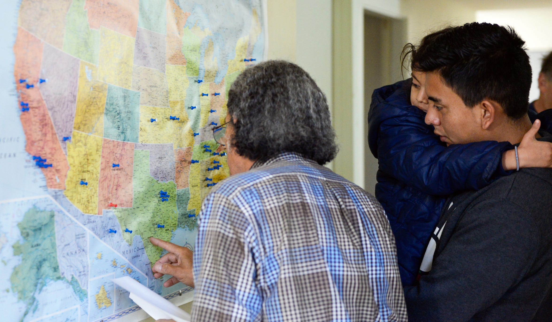 Anselmo Delgado-Martinez shows a migrant the route of his trip to live with family in December 2018 at El Calvario Methodist church in Las Cruces.