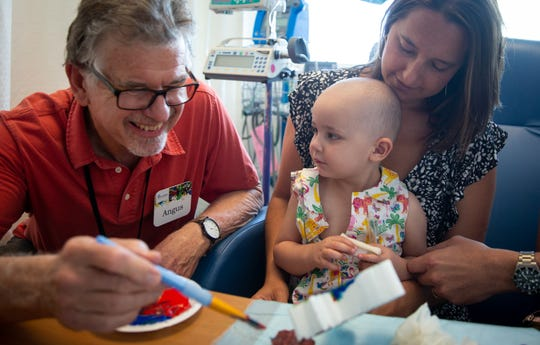 Maya Salviotti, 2, works with pediatric oncology resident artist Angus Macpherson at the UNM Children's Hospital.