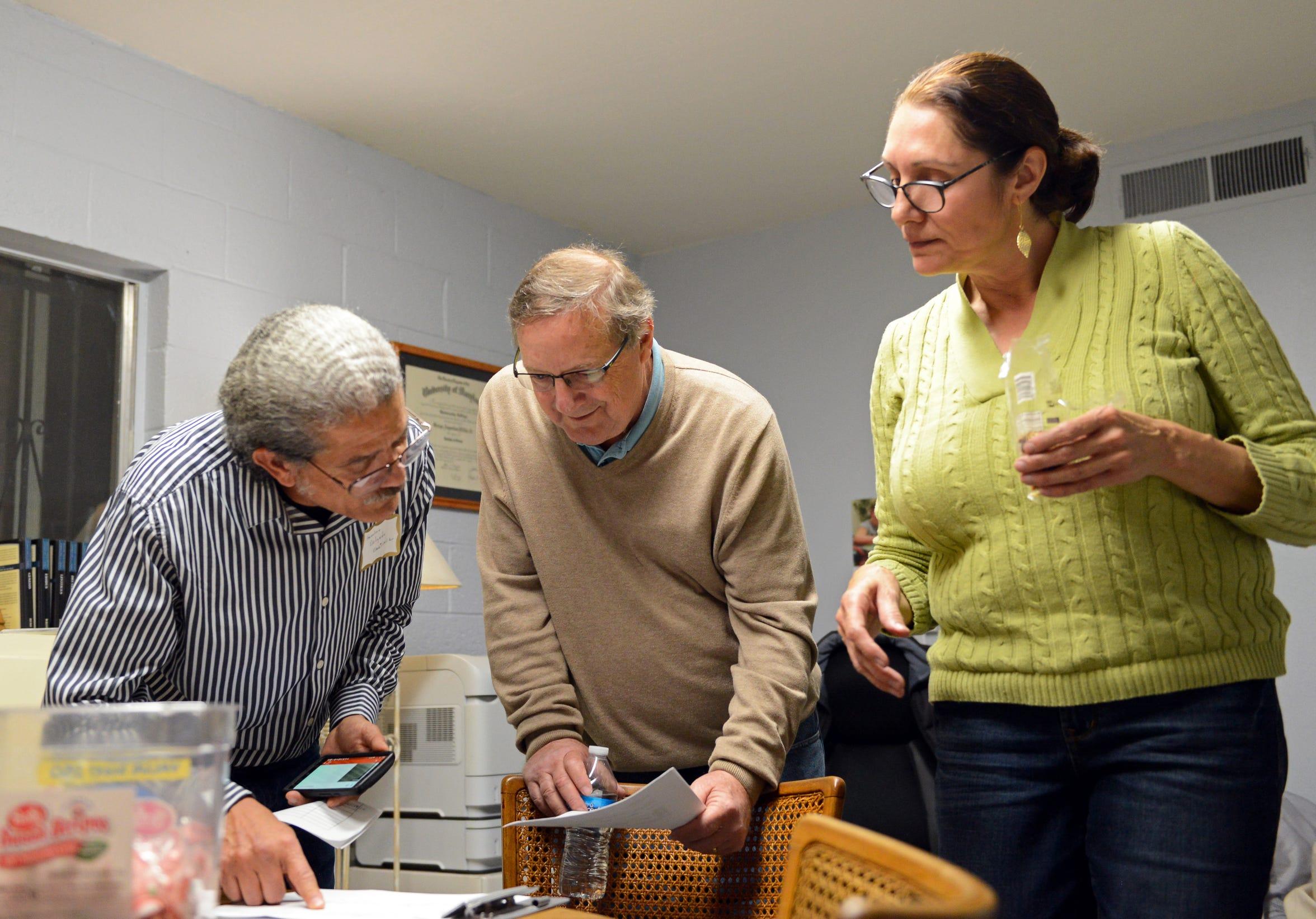Anselmo Delgado-Martinez, left, speaks to George Miller, pastor at  El Calvario Methodist church in Las Cruces, center, and a volunteer in December 2018.