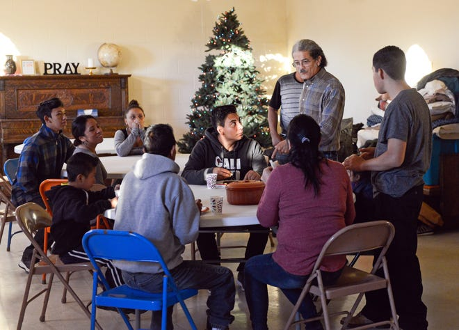 Anselmo Delgado-Martinez, standing with glasses, speaks to Central American migrants in December 2018 at El Calvario Methodist Church in Las Cruces.