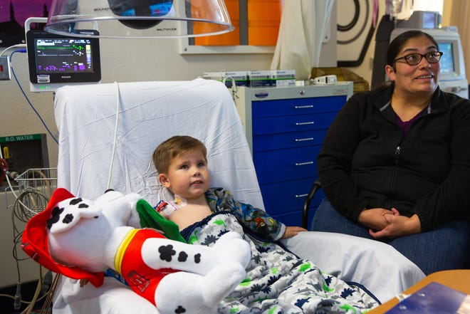 Samuel Brady, 4, watches cartoons with his mother Michelle Brady during infusion treatment at UNM Children's Hospital.