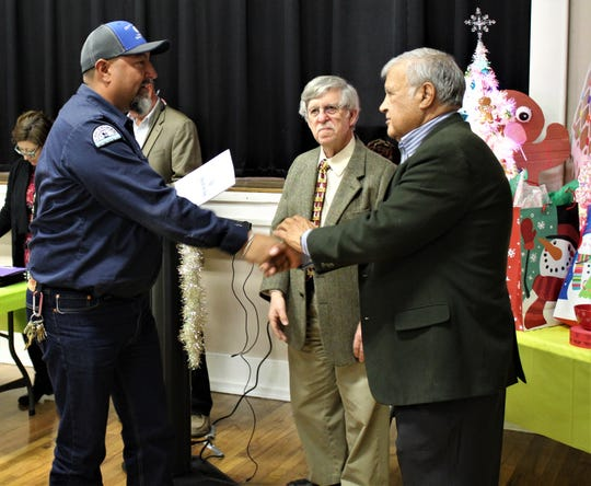 Hector Lozoya, heavy equipment operator, receives his award from Ed Archuleta, vice chairman of the LCU Board of Commissioners, with Chairman William Little looking on. Lozoya is one of the team awarded with the LCU Cost- Effective Savings Solution Award for 2018.
