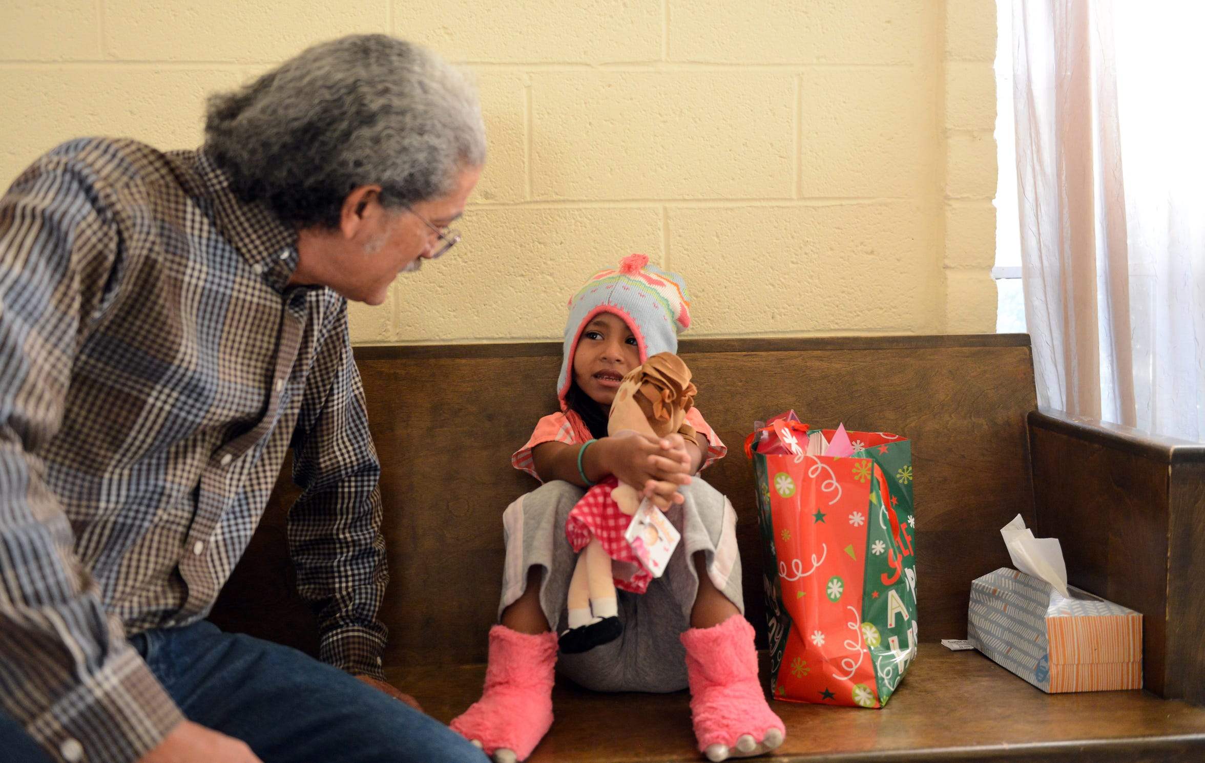 Anselmo Delgado-Martinez speaks to a 4-year-old Guatemalan girl in December 2018 at El Calvario Methodist church in Las Cruces.