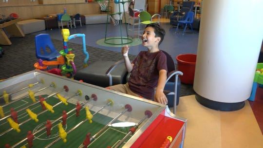 A child plays foosball at the Child Life area of UNM Children's Hospital.