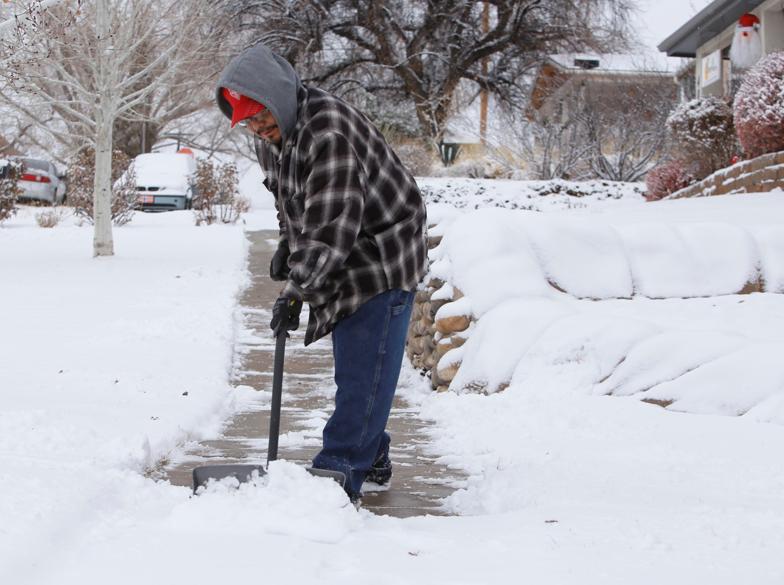 Preston Harrison, head maintenance for BeeHive Homes of Farmington, clears the sidewalk in front of the facility on north Locke Avenue on Friday.