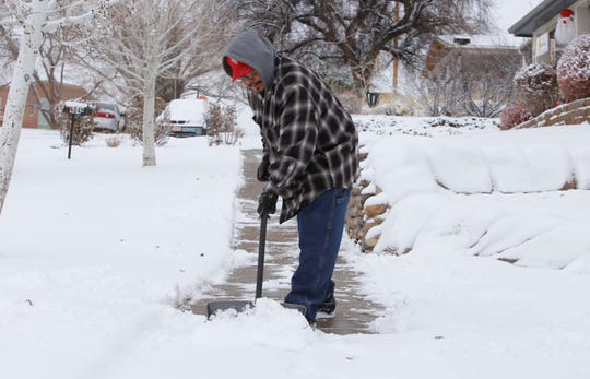 Preston Harrison, head of maintenance for BeeHive Homes of Farmington, clears the sidewalk in front of the facility on North Locke Avenue on Friday.