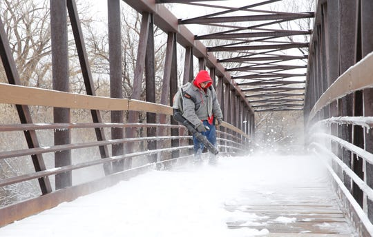 Leonard Potter, field maintenance for the city of Farmington parks and recreation department, clears snow from the Animas Bridge at Berg Park on Friday.