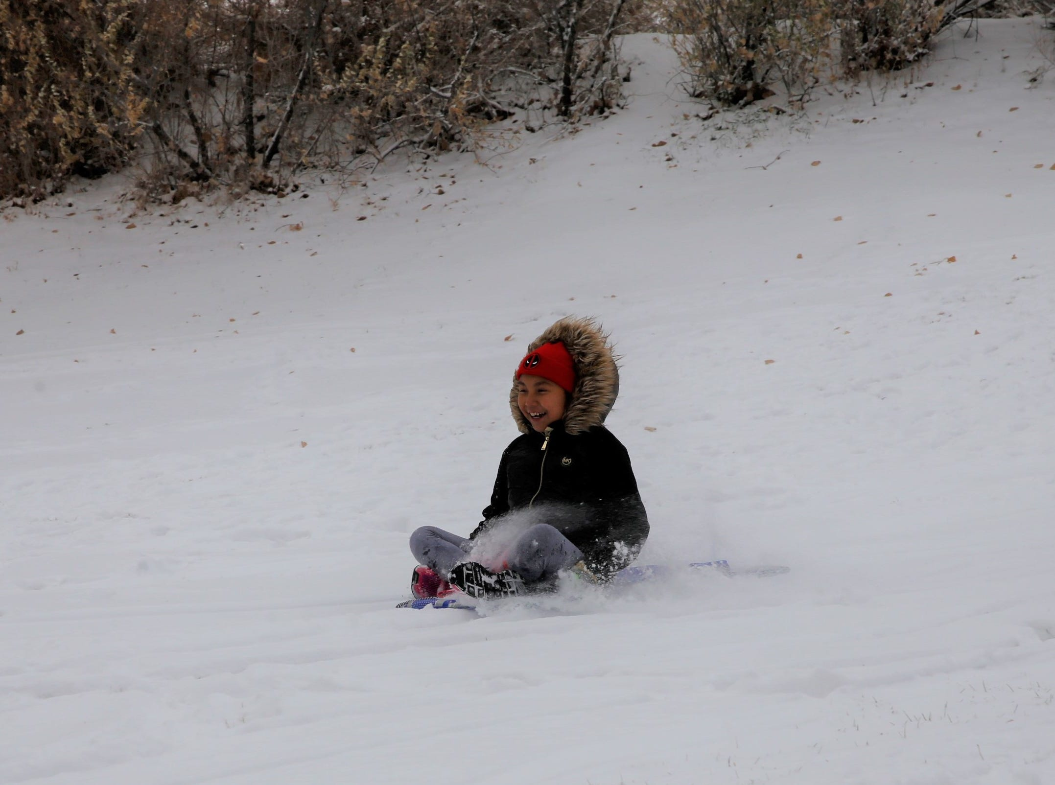 Leyiah Largo glides down a hill on Friday at Kiwanis Park in Farmington.