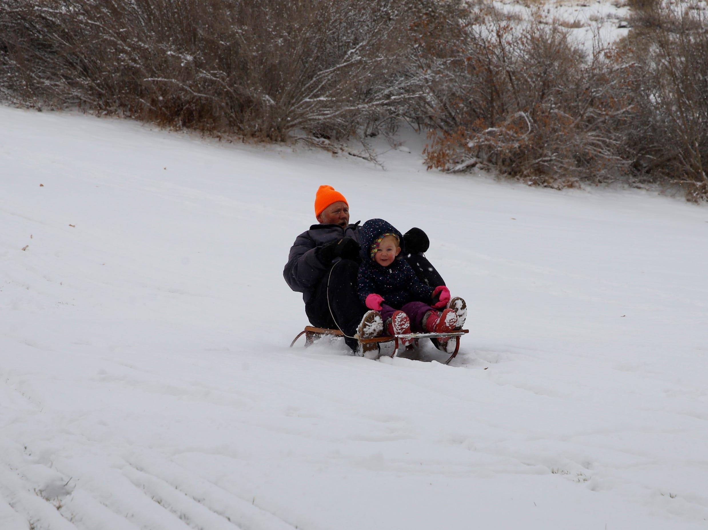 Ken McDonald took his three-year-old granddaughter sledding on Friday at Kiwanis Park in Farmington.