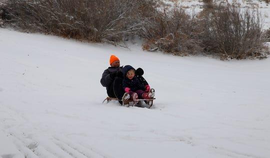 Ken McDonald took his 3-year-old granddaughter sledding on Friday at Kiwanis Park in Farmington.