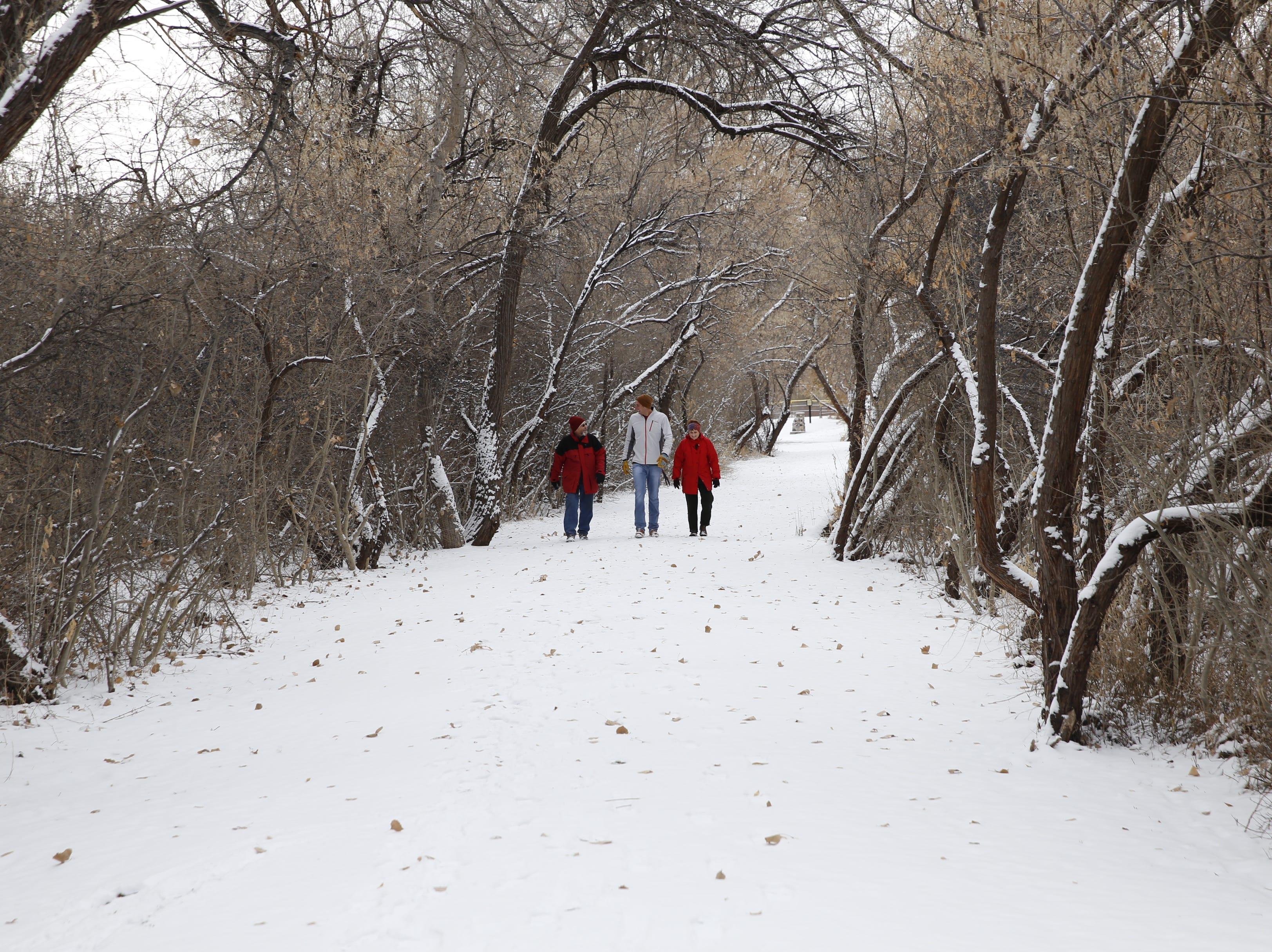 Randy McDowell, left, Connor McDowell and Teresa McDowell walk a trail on Friday in Animas Park in Farmington.
