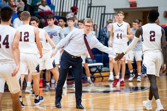 New Oxford head coach Sean Bair greets his players as they head to the bench for a timeout against Dover in the New Oxford Holiday Tournament on Thursday, December 27, 2018. The Colonials won 49-41.