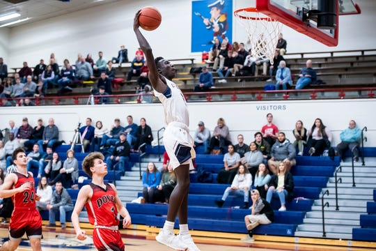In this file photo, New Oxford's Abdul Jenneh attempts a dunk during play against Dover in the New Oxford Holiday Tournament on Thursday, December 27, 2018. The Colonials won 49-41.