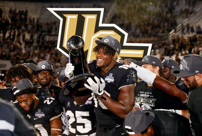 Dec 1, 2018; Orlando, FL, USA; UCF Knights defensive lineman Titus Davis (10). Holds up the champions trophy following a win over Memphis Tigers at Spectrum Stadium. Reinhold Matay-USA TODAY Sports