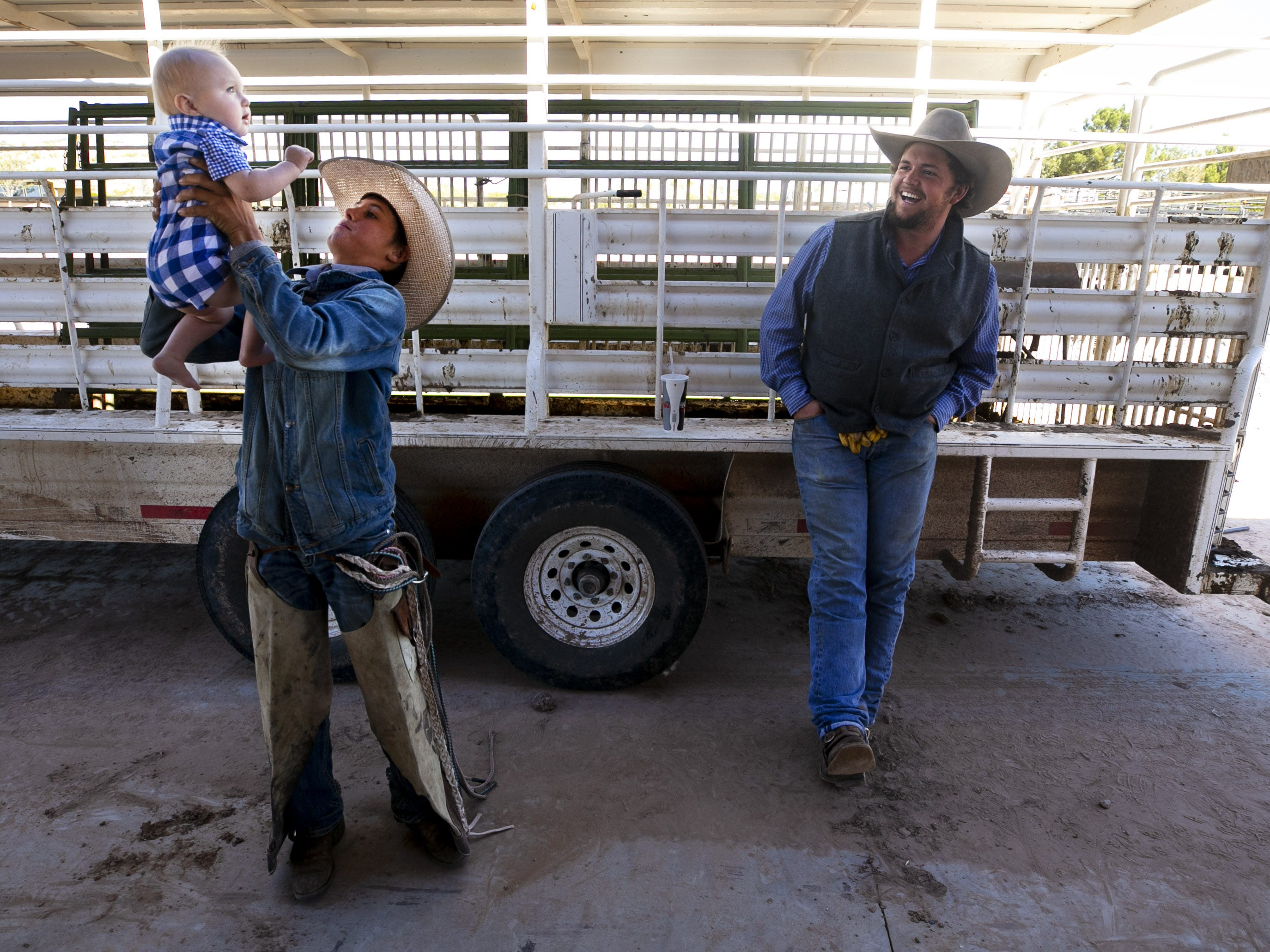 Cowboy Trevor Bellamy, 15, holds his nephew, Leighton Goodman, 9 months, as fellow Lady B Ranch cowboy Clayton Davis looks on at the Lazy B Ranch outside of Duncan, Ariz., on Nov. 2, 2018. Former Supreme Court Justice Sandra Day O'Connor grew up on the ranch.