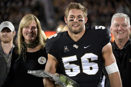 Central Florida linebacker Pat Jasinski (56) is escorted onto the field by his family during Senior Night festivities before an NCAA college football game against Cincinnati Saturday, Nov. 17, 2018, in Orlando, Fla. (AP Photo/Phelan M. Ebenhack)