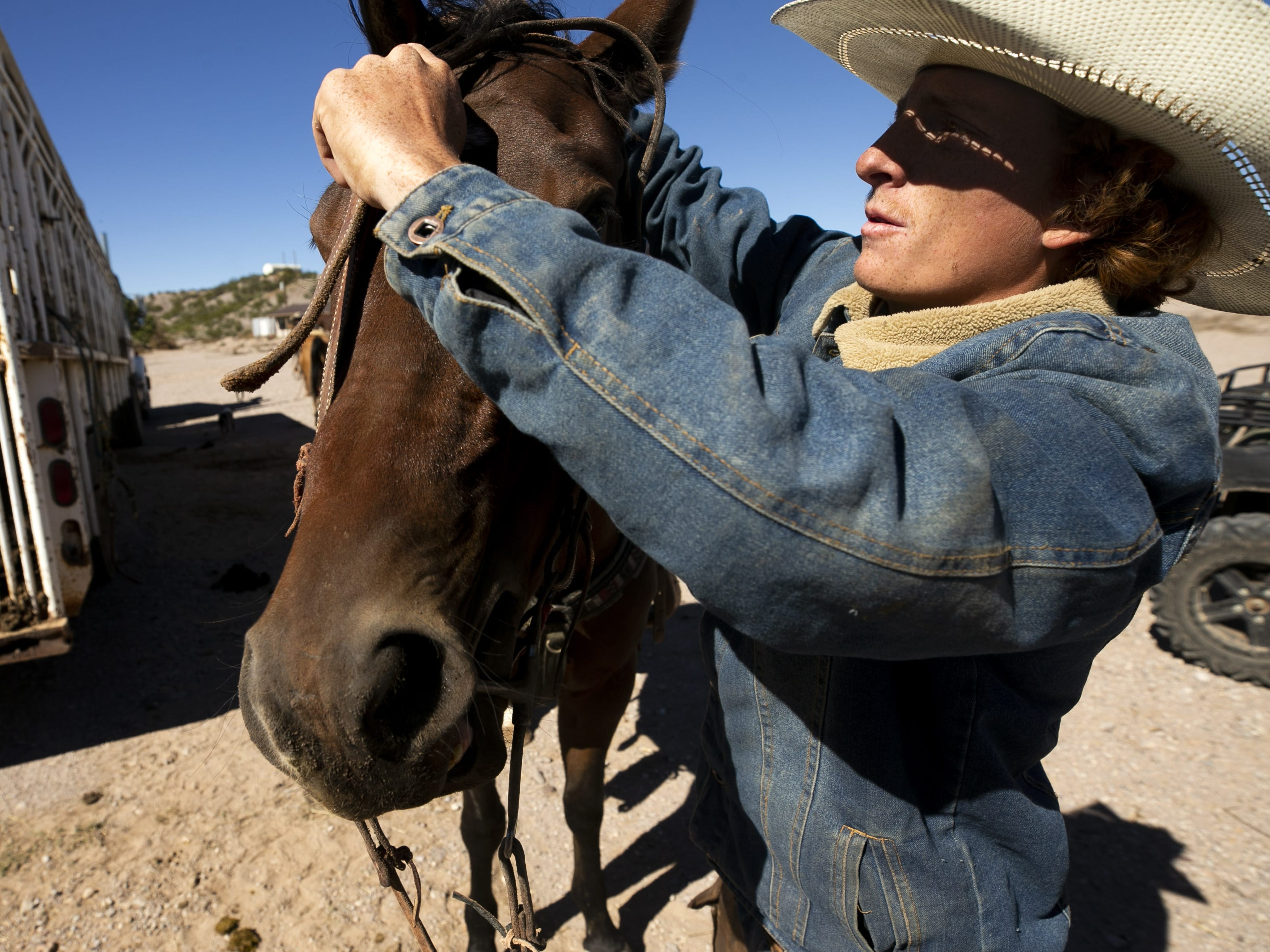 Cowboy Payson Harsh, 18, gets his horse ready before a roundup of cattle at the Lazy B Ranch outside of Duncan, Ariz., on Nov. 2, 2018. Former Supreme Court Justice Sandra Day O'Connor grew up on the ranch.