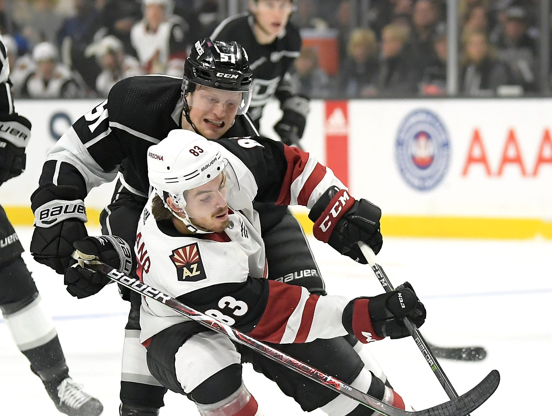 Los Angeles Kings left wing Austin Wagner, top, reaches for the puck in front of Arizona Coyotes right wing Conor Garland during the first period of an NHL hockey game Thursday, Dec. 27, 2018, in Los Angeles. (AP Photo/Mark J. Terrill)