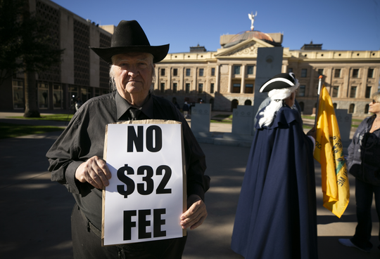 Mark Spear of Tucson protests the new $32 vehicle registration fee at the Arizona state Capitol in Phoenix on Dec. 28, 2018.