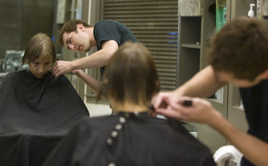 Madison Avenue International Salon & Day Spa hairstylist Devin Fox gives Ahwatukee resident Eric Neufeld a haircut. Arizona's minimum wage for waiters, bartenders, valets, hairstylists and other tipped employees will be $8 starting in 2019.