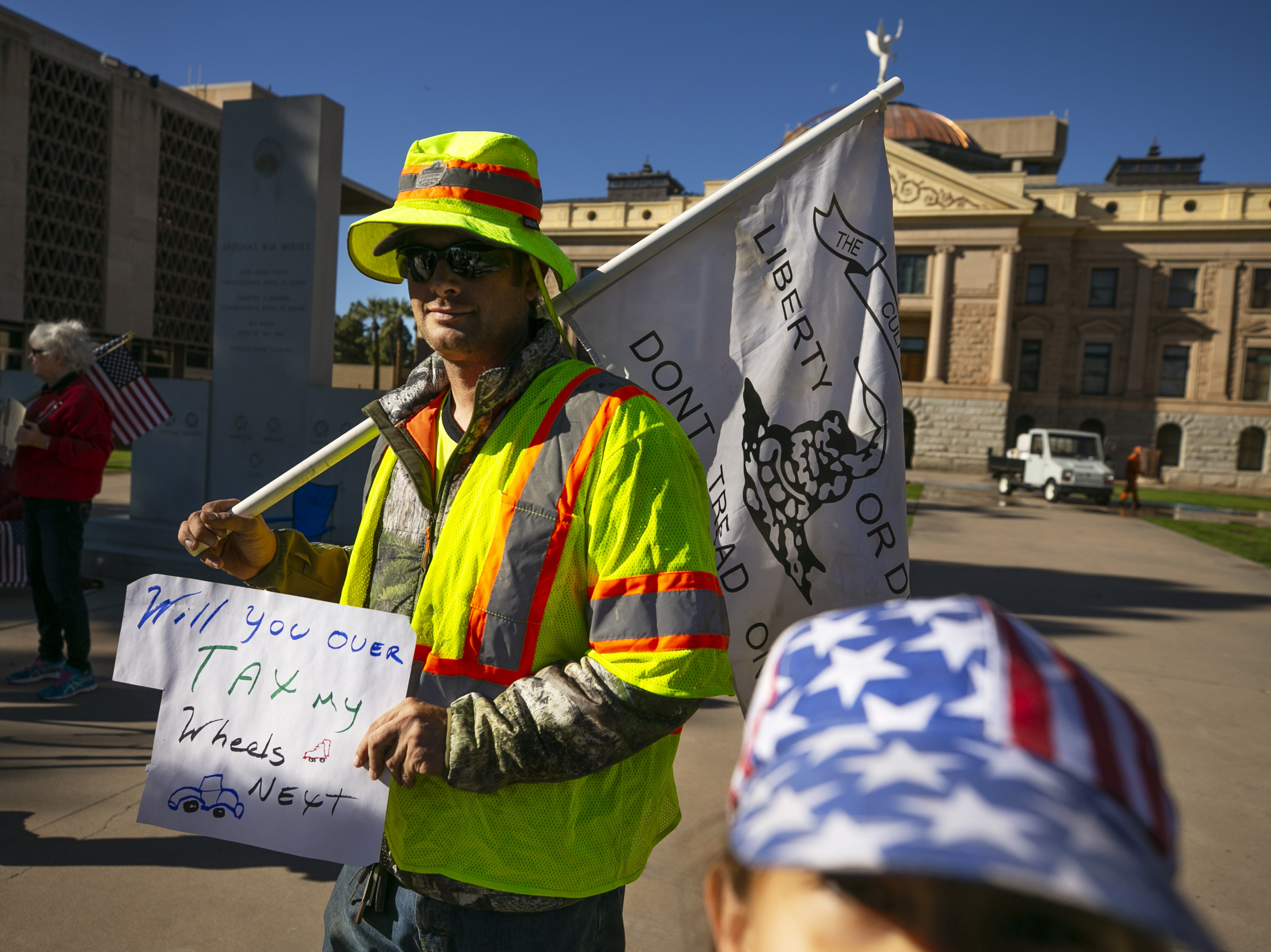 Bryon McComb and his daughter Kathryn McComb, 9, of Phoenix, protest the new $32 vehicle-registration fee at the Arizona state Capitol in Phoenix on Dec. 28, 2018. Protesters argue it's an illegal tax that was not approved by two-thirds of both chambers of the state Legislature.