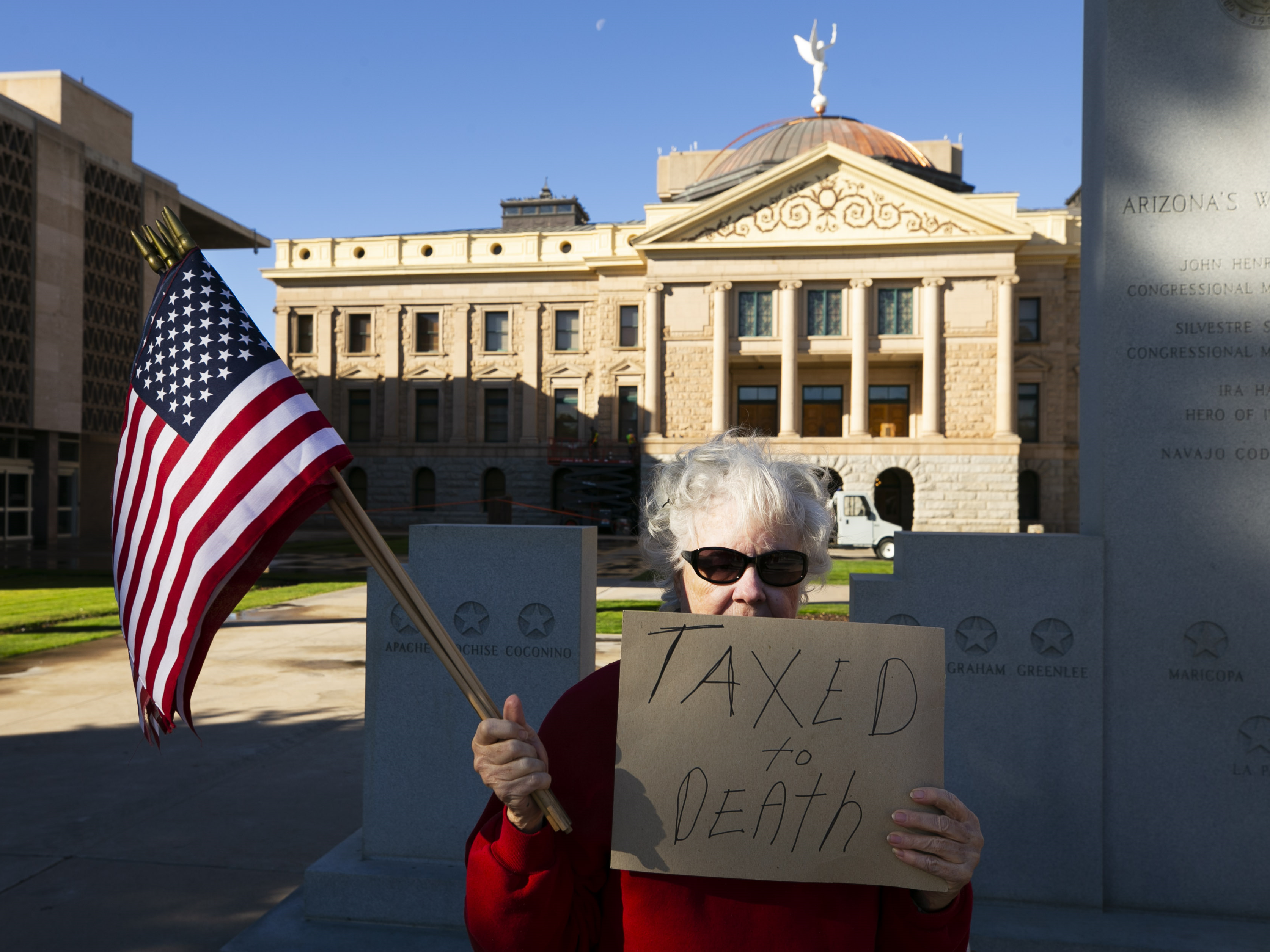 Kathryn Kobor of Phoenix and other protesters voice their opinion against the new $32 vehicle-registration fee at the Arizona state Capitol in Phoenix on Dec. 28, 2018.
