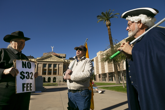 Mark Spear of Tucson (from left), Nohl Rosen of WIckenburg and Patrick Lacey of Maricopa protest the new $32 vehicle-registration fee at the Arizona state Capitol in Phoenix on Dec. 28, 2018. Protesters argue it's an illegal tax that was not approved by two-thirds of both chambers of the state Legislature.