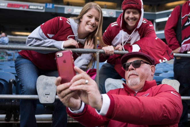Arizona Cardinals head coach Bruce Arians takes a photograph with fans before the start of a game against the Seattle Seahawks at CenturyLink Field last season.
