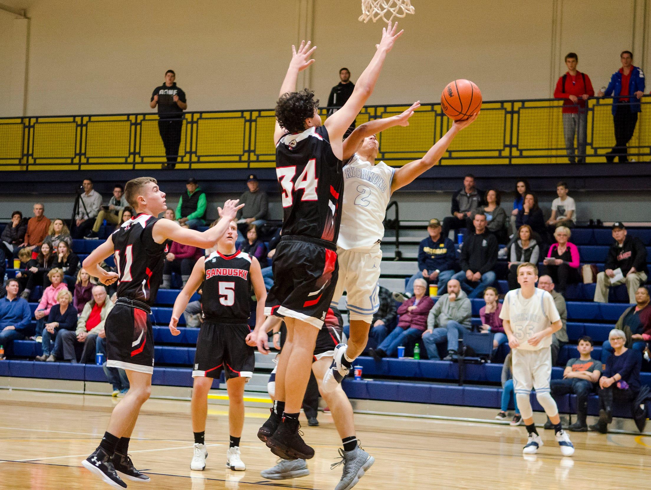 Sandusky High School forward Tyler Nelson (34) jumps to block a basket by Richmond High School guard Drew Davis during their SC4 Holiday Basketball Showcase game Friday, Dec. 28, 2018 at the SC4 Fieldhouse.