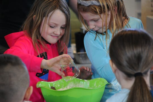 Leah Ball and Libby Manceau mix a science experiment at the Wacky Winter Science event at Fort Gratiot Light Station County Park.