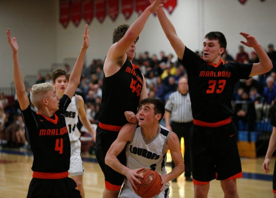 Lourdes' George Siegrist is covered by, from left, Marlboro's Daniel Rusk, Matthew Jackson and Anthony Musacchio during Friday's game in the Duane Davis Tournament at Roy C. Ketcham High School on December 27, 2018.