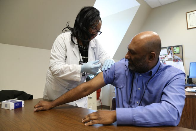 Registered Nurse Arlissa Morrison demonstrates how to administer the flu vaccine on Dr. Anil Vaidian commissioner of Behavioral and Community Health in the City of Poughkeepsie on December 27, 2018.