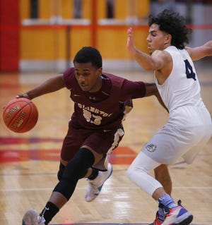 Arlington's Rashawn Grant drives through Beacon's Aaron Davis during a Duane Davis Basketball Tournament game on Dec. 27, 2018.