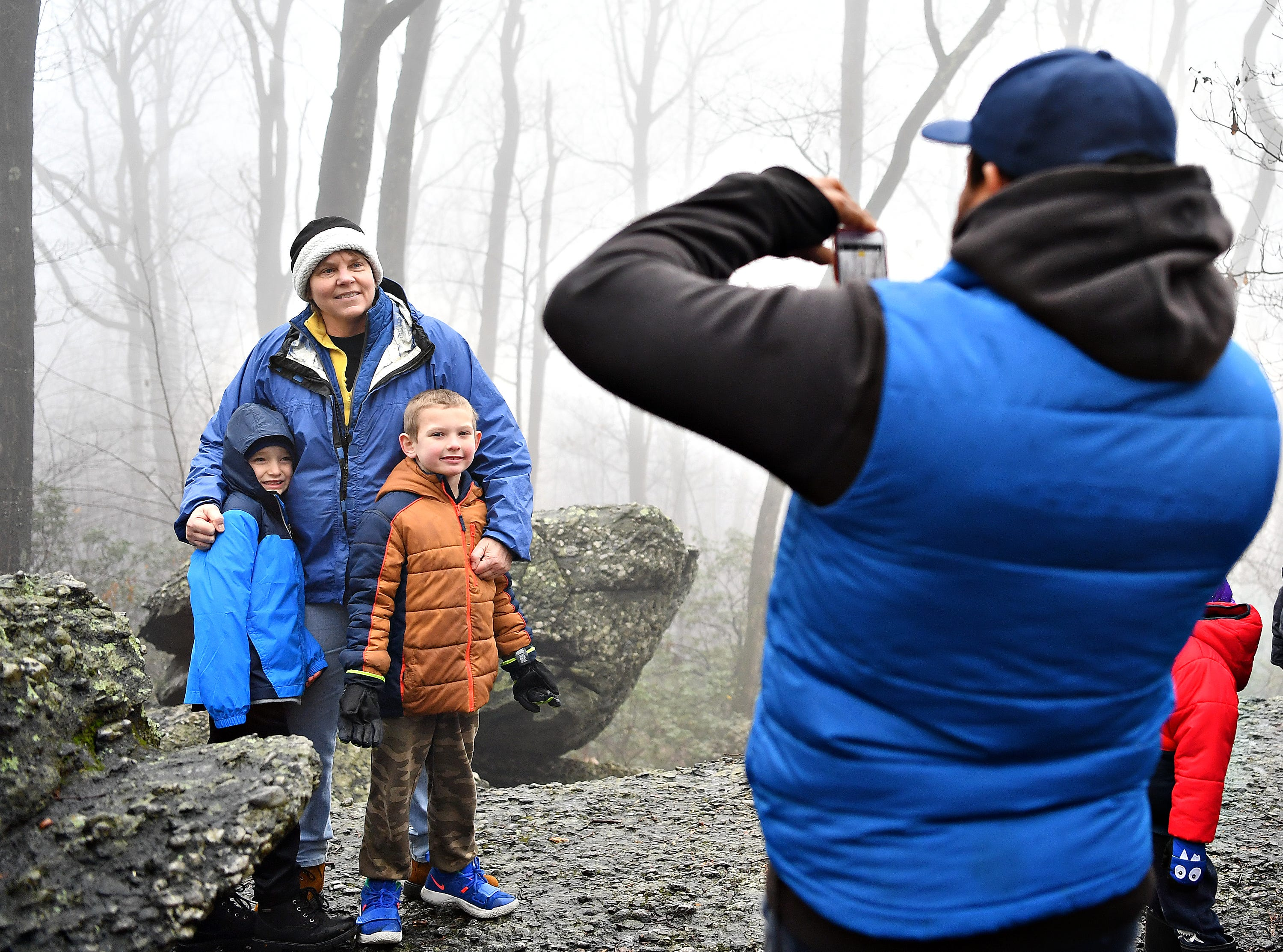 Tanya Merchant, back left, of East Manchester Township, poses for a photo with her great-nephew Mason Zercher, 6, front left, and neighbor Lucas Buckler, 6, during a Marshmallow Hike led by York County Parks Naturalist Kelsey Frey at Rocky Ridge Park in Springettsbury Township, Friday, Dec. 28, 2018. Dawn J. Sagert photo